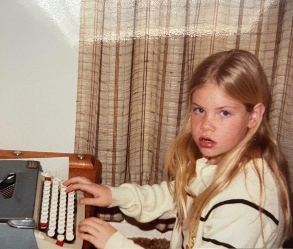 10 year old Monya sitting at a typewriter